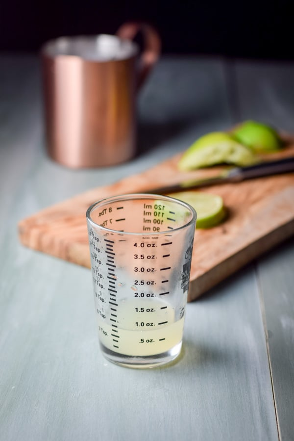 lime juice squeezed and measured with lime in the background and a copper mug
