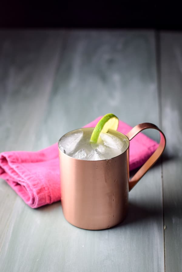 A copper mug filled with a Moscow mule with a lime on the rim