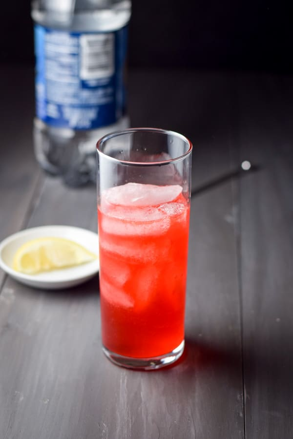 Sloe gin fizz poured into a glass awaiting the club soda