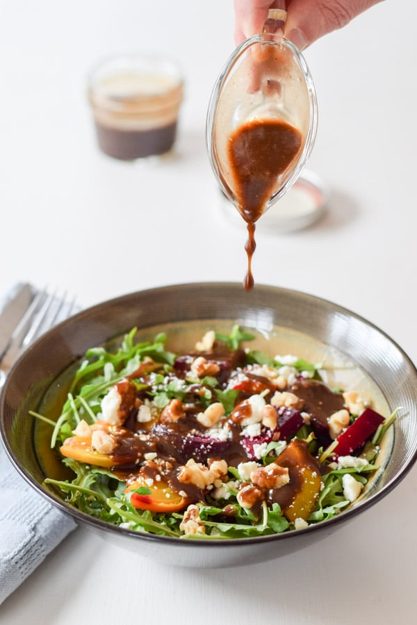 Putting the dressing on the awesome colorful arugula beet salad