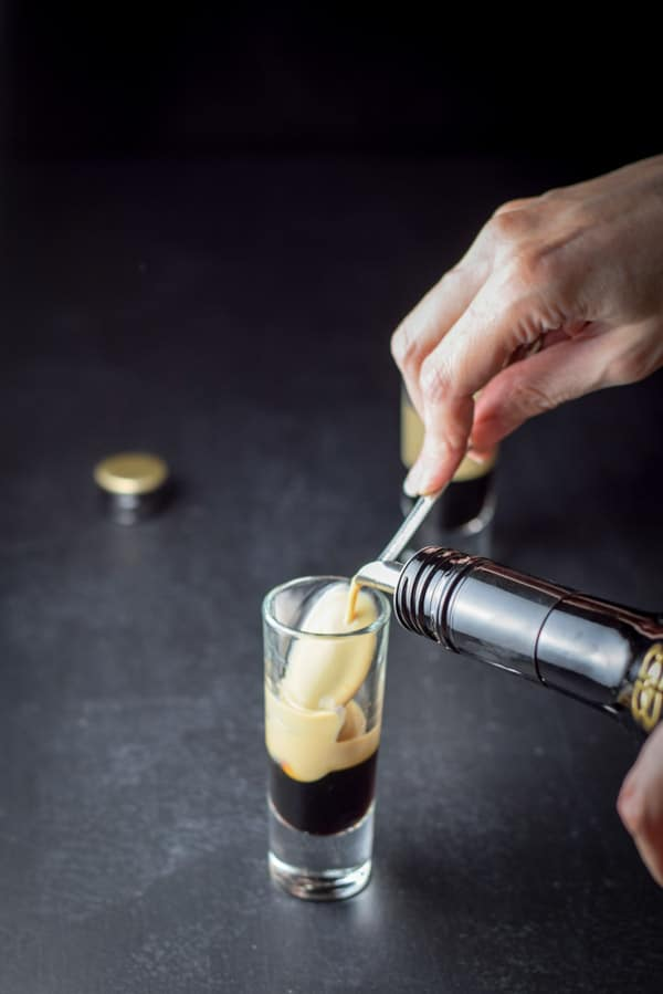 Pouring Baileys Irish Cream for the party time B52 shot recipe
