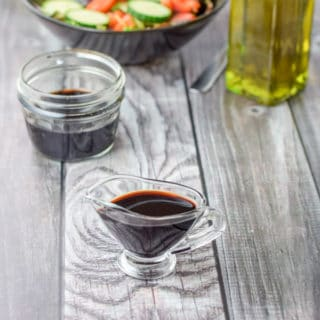 Balsamic vinegar reduction ready to be poured on a salad.