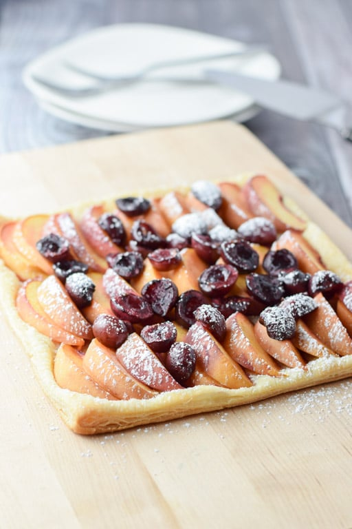 Confectioner's sugar on the yummy cherry and peach tart