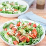 Salad dressing on the arugula spinach strawberry pecan salad