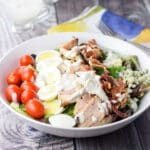 Blue cheese dressing fully poured onto the colorful lined salad with dressing in a container