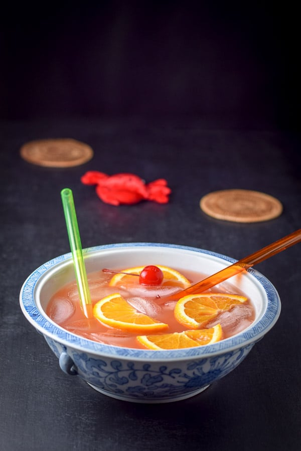 Bowl of scorpion bowl recipe with fruit in it and straws