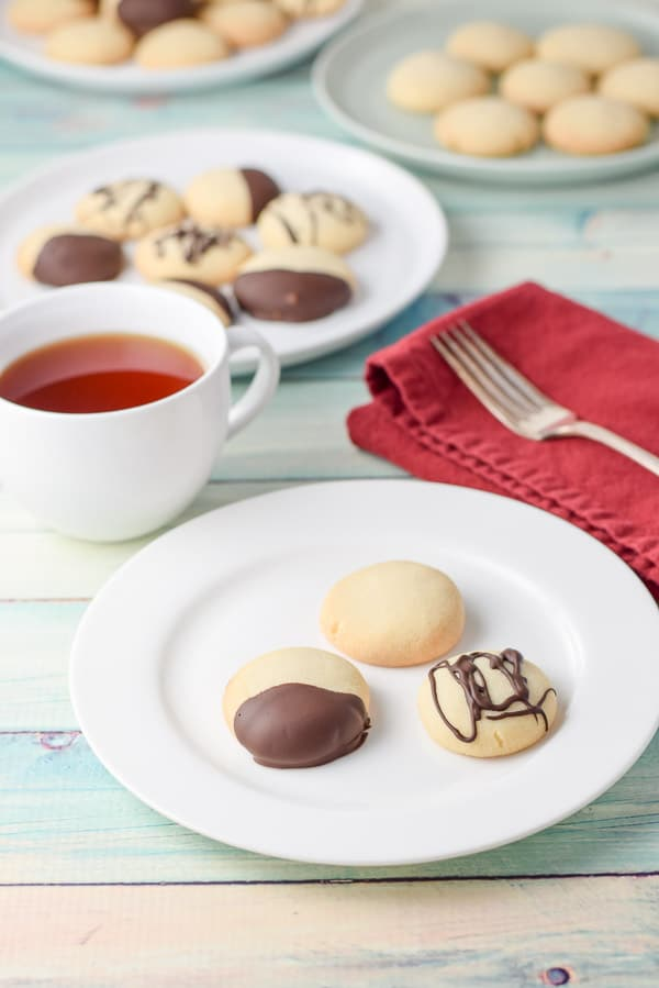 3 butter shortbread cookies plated with a cup of tea near them
