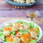 Dressing poured for the sweet orange scallop salad