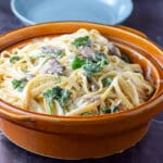 A big brown bowl of fettuccine with mushrooms and spinach with two bowls in the background - Square