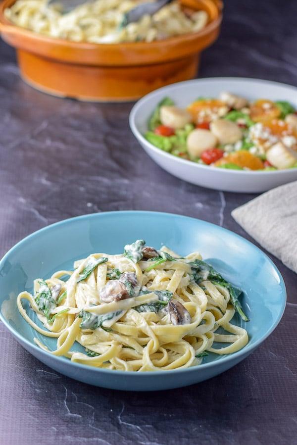 Plated spinach and mushroom fettuccini alfredo