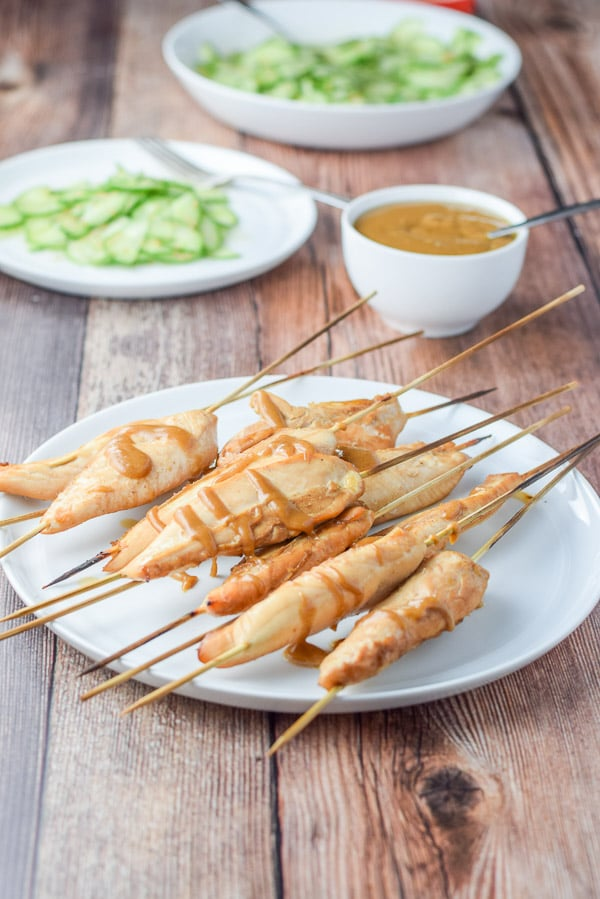 Thai chicken satay done and dribbled with peanut sauce with a bowl of it in the background
