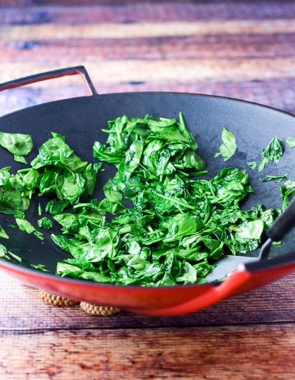Spinach sautéed in a red wok for the spinach and crab quesadillas