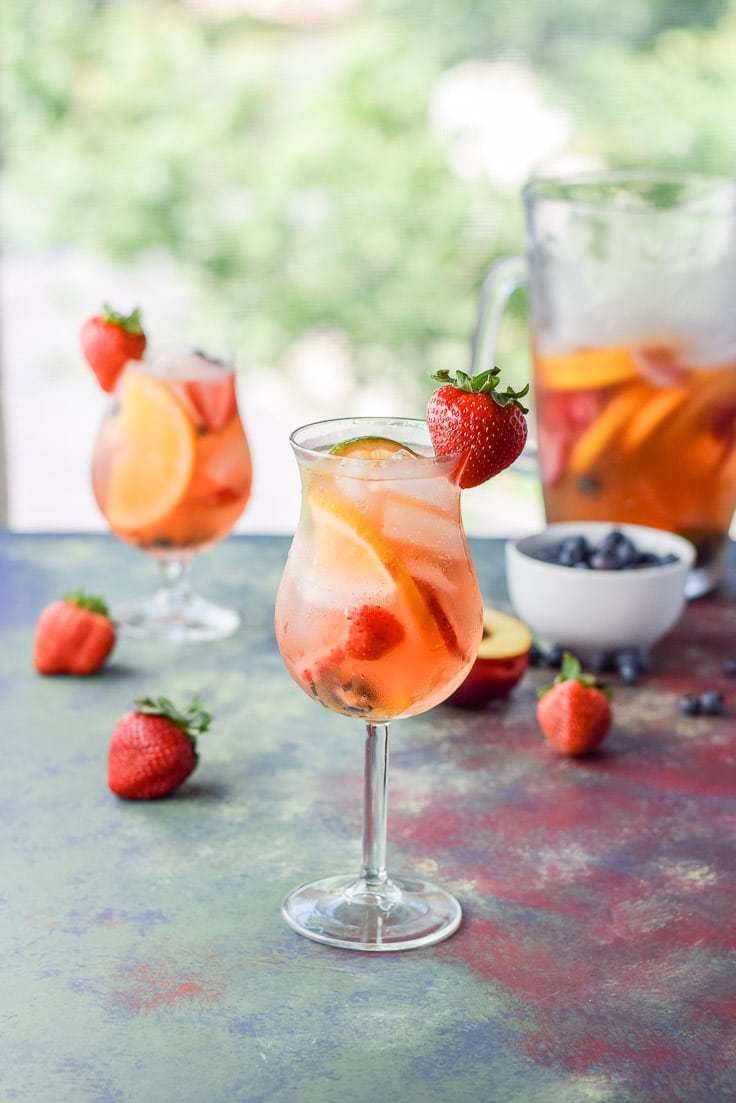 Fabulous fruity white sangria garnished with a strawberry and ready to be sipped