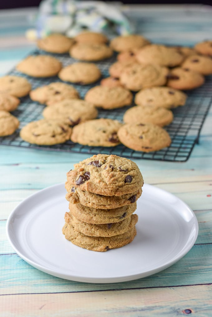 Pile of chocolate chip cookies with a rack of chocolate chip cookies in the background
