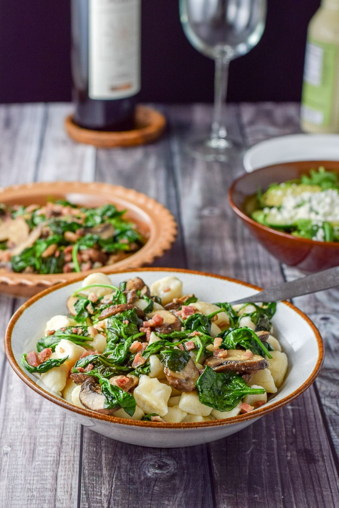 Gnocchi with Pancetta Mushroom and Spinach served in a big bowl with so many yummies in the background!