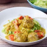 A white plate with meatballs in a curry sauce on zoodles - square