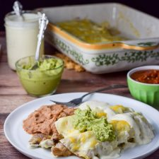 Guacamole and more sour cream sauce draped over the easy chicken enchiladas with sour cream sauce ready to be eaten.