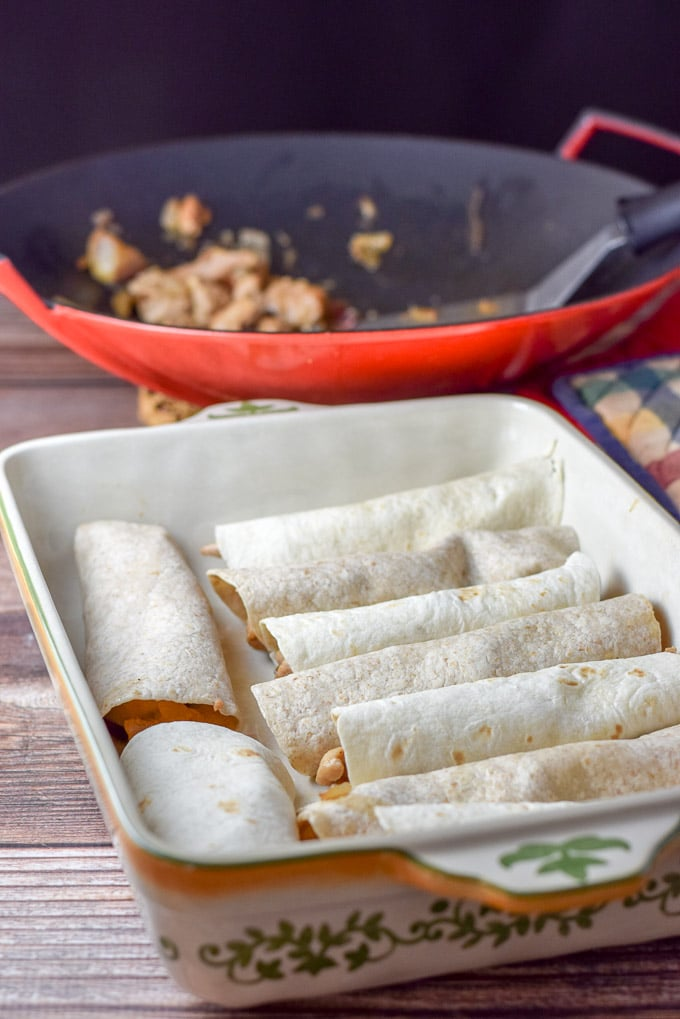 Line up of chicken enchiladas with white sauce, but without the sour cream sauce