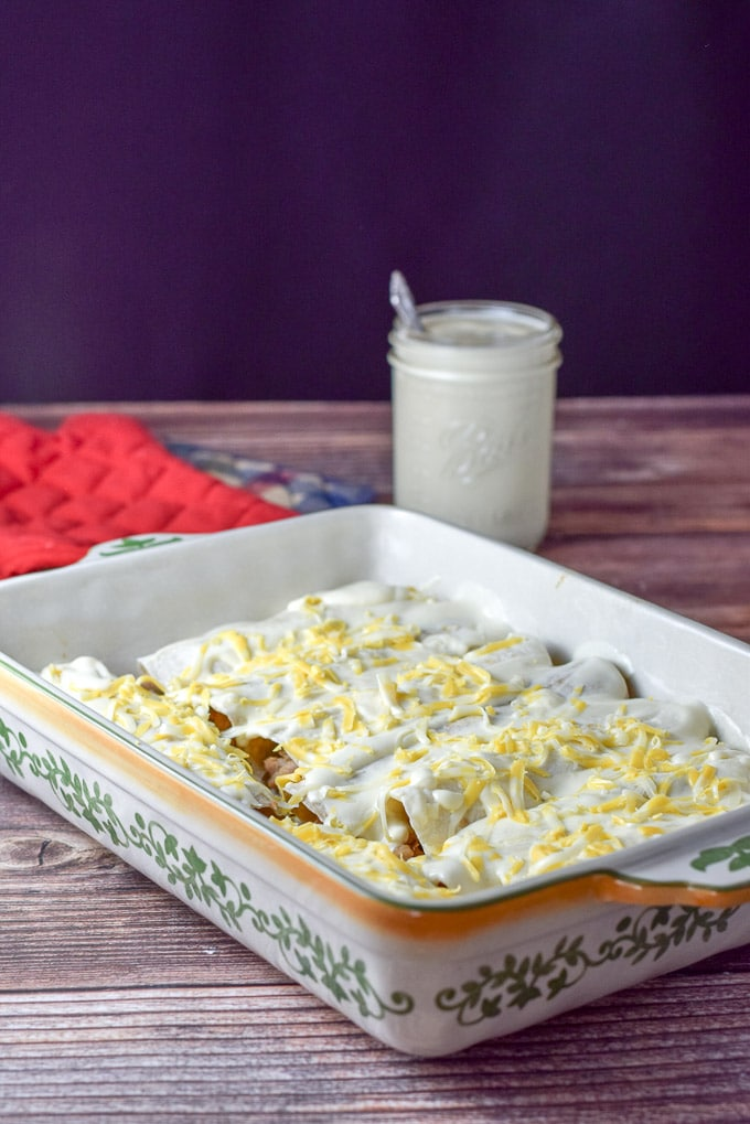 Baking dish with chicken enchiladas with white sauce lined up. Sour cream sauce is poured on along with sprinkles of cheese for the chicken enchiladas with white sauce