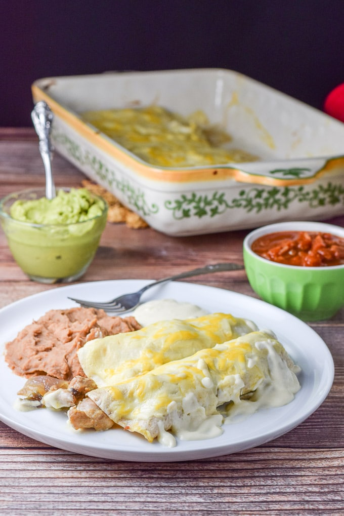 Plated easy chicken enchiladas with white sauce with refried beans and some extra sour cream sauce draped across