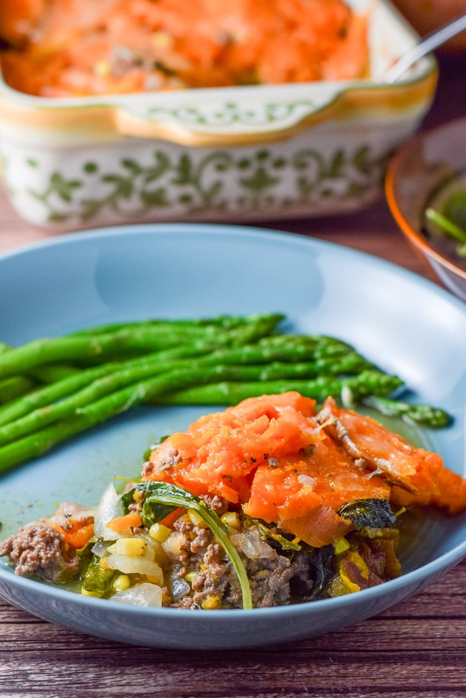 The three cheers for shepherd's pie casserole plated with some asparagus