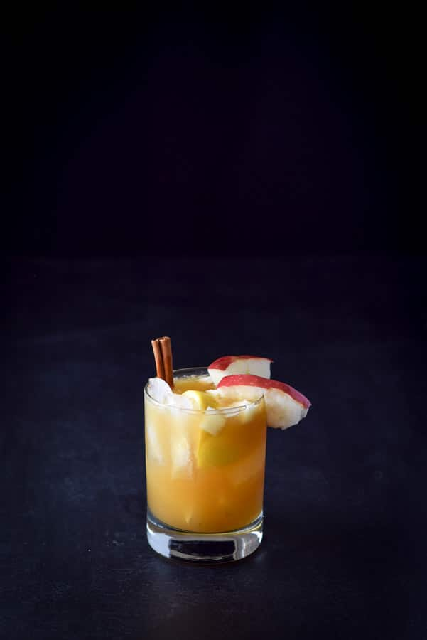 Apple cider bourbon smash cocktail poured in the glass and garnished with half an apple and cinnamon stick