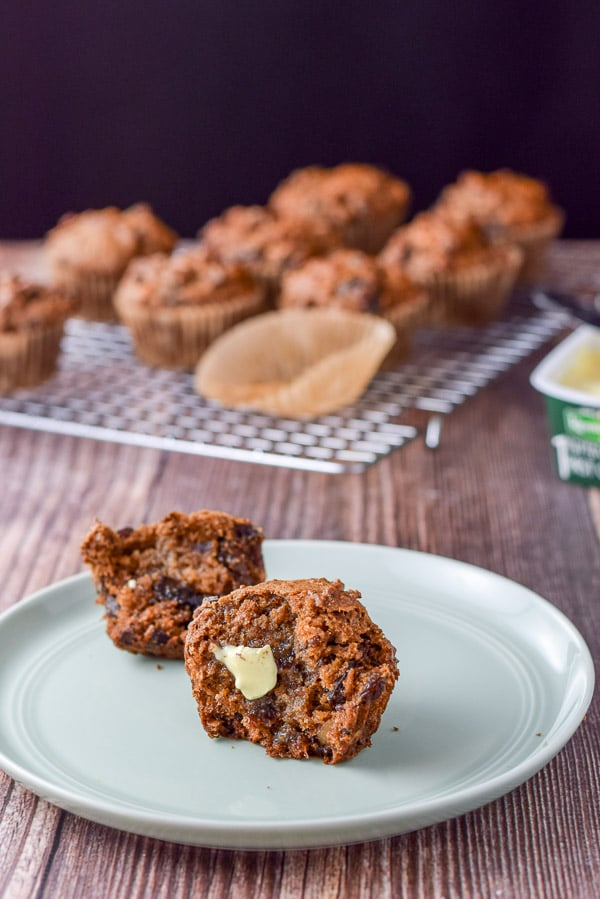 Butter on one of the delish date nut muffins on a green plate