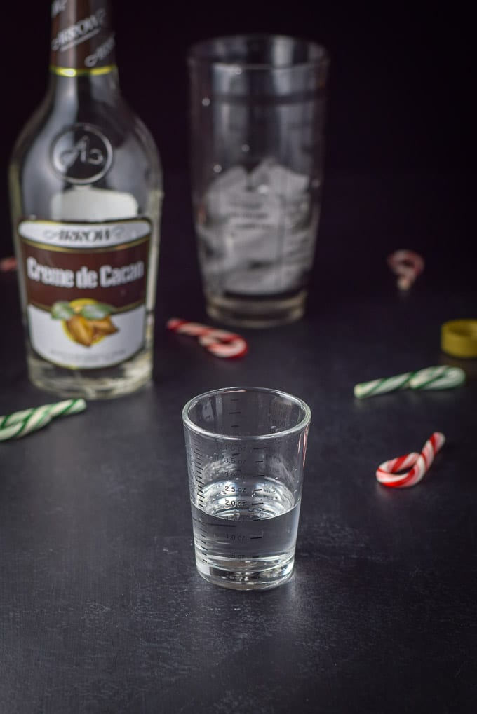 Creme de Cacao poured out for the holiday chocolate candy cane martini