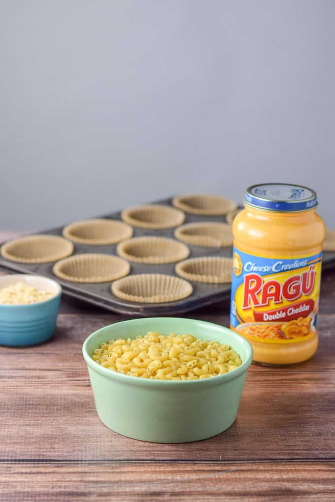 Elbow macaroni, RAGÚ Double Dheddar<sup>®</sup> and some muffin tins in the background