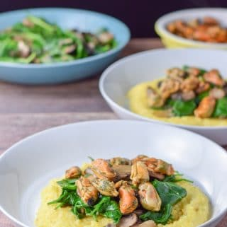 2 bowls of mushrooms, spinach and mussels on creamy polenta