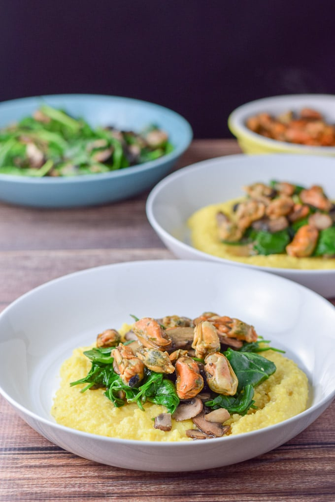 2 bowls of mushrooms, spinach and mussels with wine sauce on creamy polenta