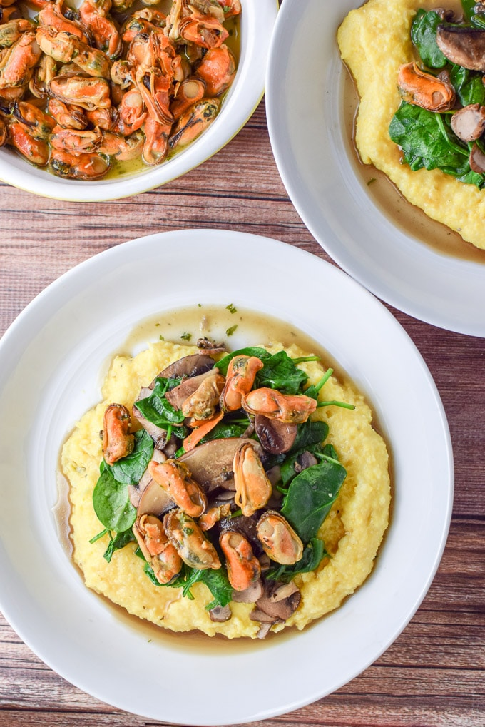 Overhead view of the 2 bowls of mushrooms, spinach and mussels on creamy polenta