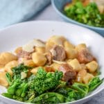 Close up of the broccoli rabe in a plate with some sausage and gnocchi