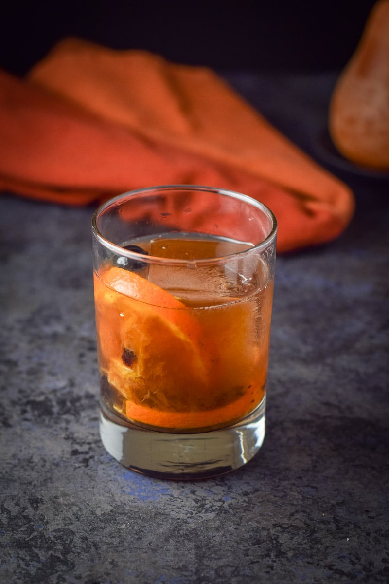 Bourbon poured in the rocks glass and all mixed for the old fashioned cocktail recipe. Orange napkin and candle in the background