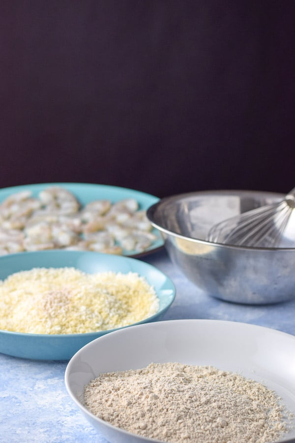 Flour in a shallow bowl, panko, flour and coconut in another shallow bowl and egg in a metal bowl for the baked coconut shrimp