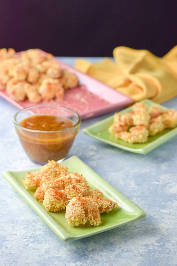 Plated baked coconut shrimp with apricot sauce in the background