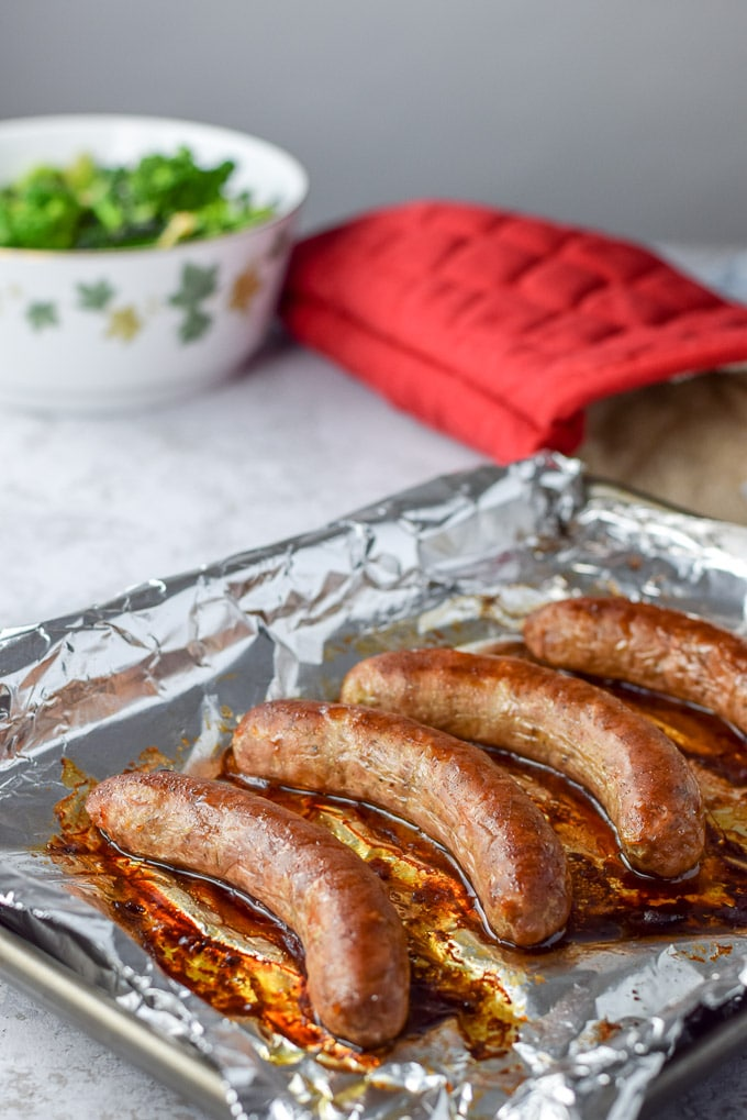 Sausage baked on a tray front and center for the gnocchi with sauce