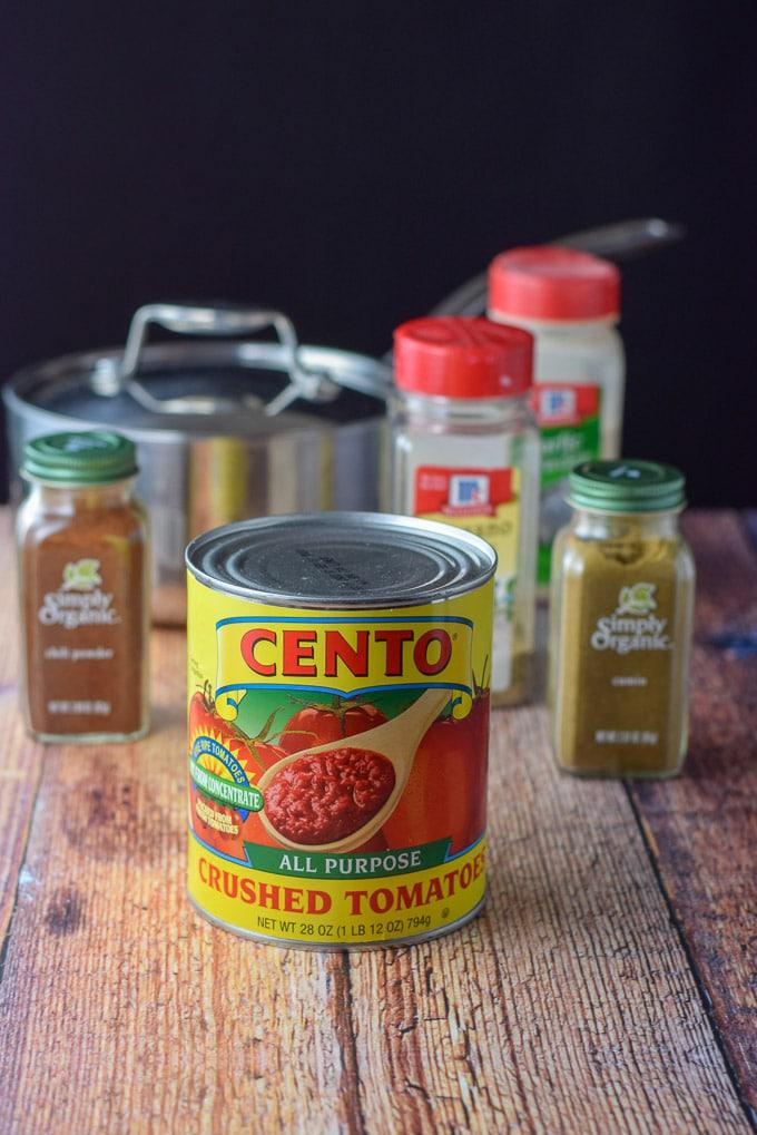Crushed tomatoes, cumin, chili powder, oregano, garlic powder and a pan for the smooth enchilada sauce