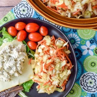 Overhead view of the Thai inspired coleslaw on a plate with chicken salad, munster cheese, lettuce and some grape tomatoes