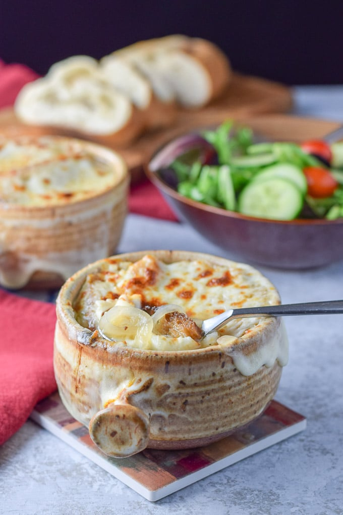 A spoon is in the crock of easy French onion soup