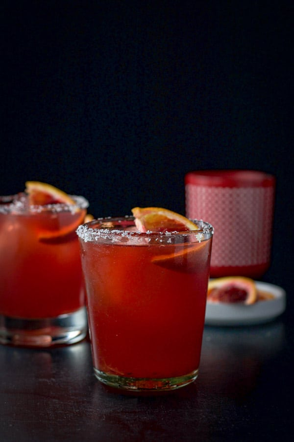 2 glasses of the blood orange margarita with orange slices in it