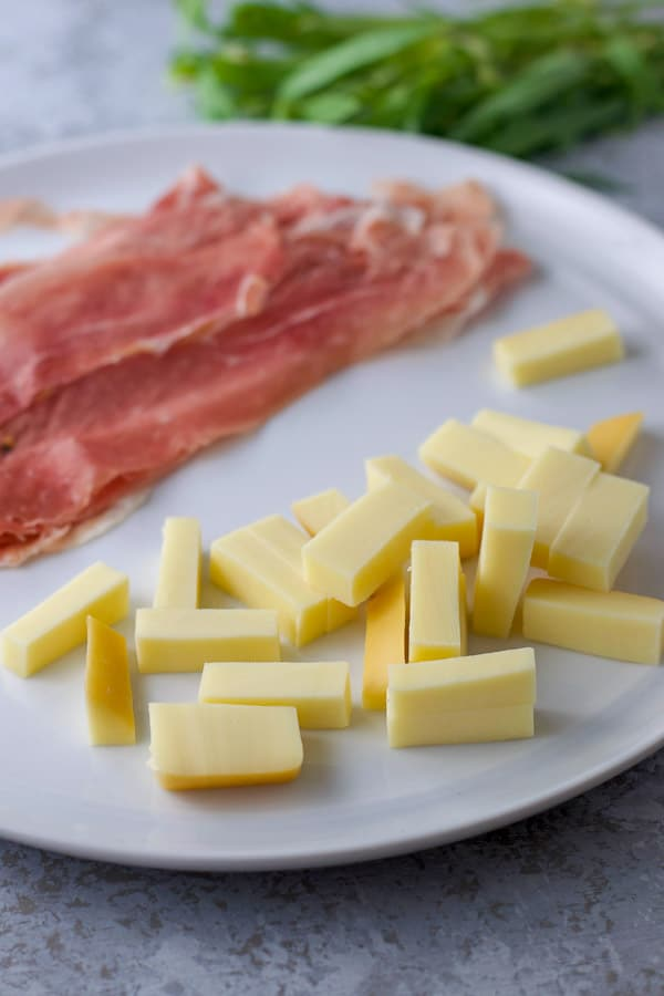 Gouda slices and prosciutto and tarragon in the background for the chicken saltimbocca recipe