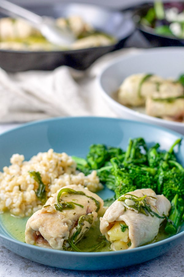 A couple of chicken saltimbocca on a plate with rice and broccoli rabe. There is the pan of chicken saltimbocca in the background for the chicken saltimbocca recipe