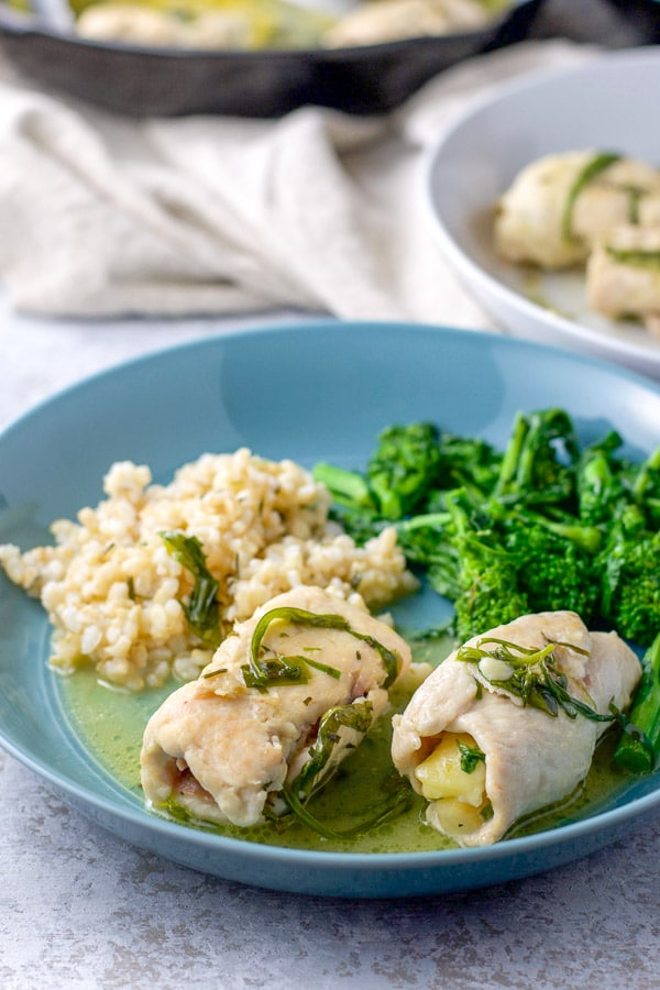 Different view of A couple of chicken saltimbocca on a plate with rice and broccoli rabe. There is the pan of chicken saltimbocca in the background - for the chicken saltimbocca recipe
