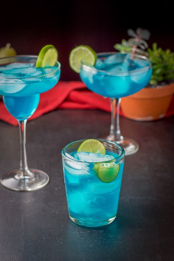 View of the three filled glasses of the electric blue margarita. There is a plant in the background and a red napkin!
