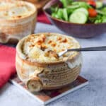 Two crocks filled with the cheesy onion soup with a spoon in the front crock - square