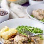 Chicken thighs with lemon plated with a potato and peas. There are beans in the background along with some another plate and the baking dish