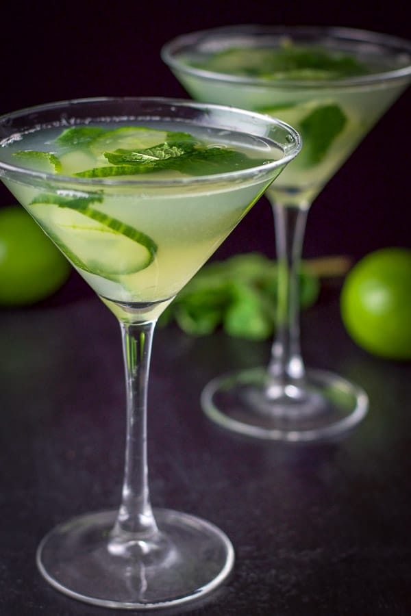 Two cucumber mint martini's poured out with some limes and mint in the background