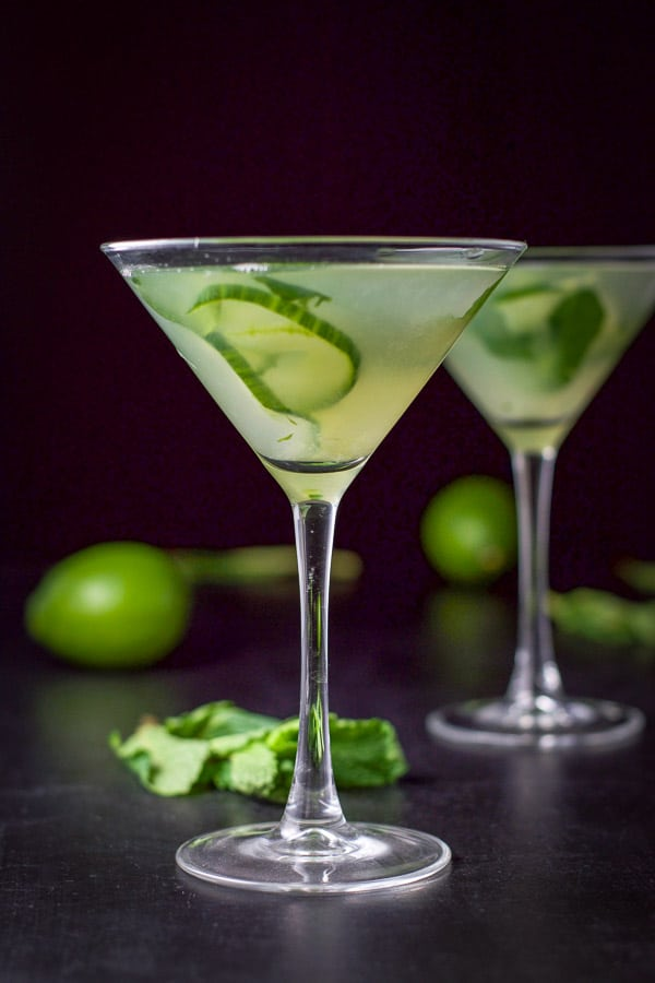 Vertical view of the cucumber mint martini with two limes and a bunch of mint