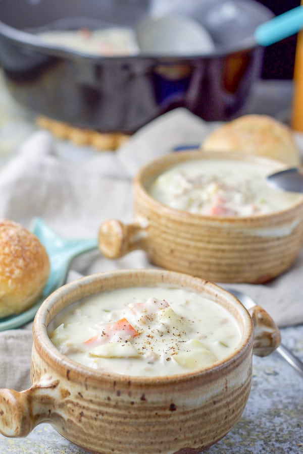 Two crocks of easy clam chowder with some fresh pepper on top. There are a few rolls and the pan of clam chowder behind them.